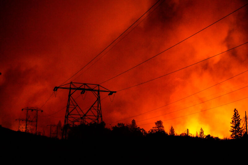 Power lines are cast in silhouette as the Creek Fire creeps up on on the Shaver Springs community off of Tollhouse Road on Tuesday, Sept. 8, 2020 in Auberry, CA.