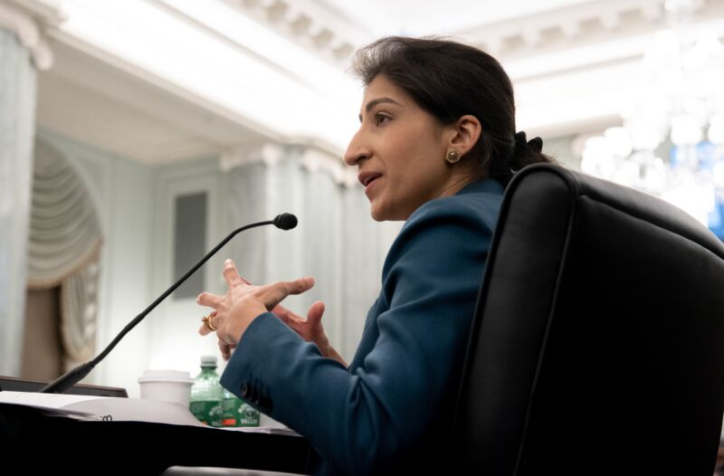Lina Khan speaking and gesturing with her hands at a Senate committee hearing.