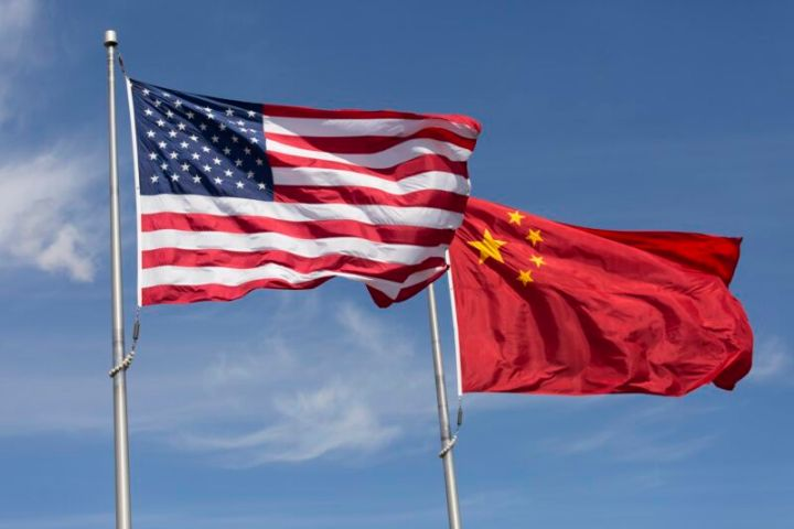 The flags of the US and China rippling on flagpoles on a windy day.