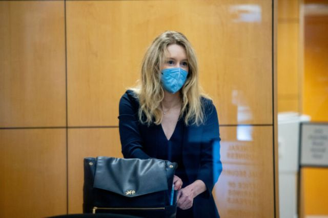 Theranos founder Elizabeth Holmes collects her belongings after going through security at the Robert F. Peckham Federal Building with her defense team on August 31, 2021, in San Jose, California.