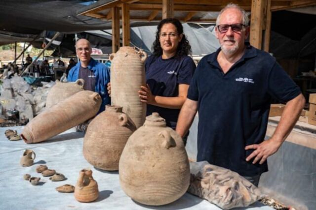 The excavation director poses with a jar of clay and other pieces recovered from the Yavne excavation.  (lr): Dr. Eli Haddad, Liat Nadav-Ziv, and Dr. John Seligman.