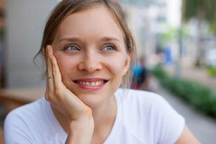 bella mujer rubia de ojos celestes sonrie y piensa positivamente
