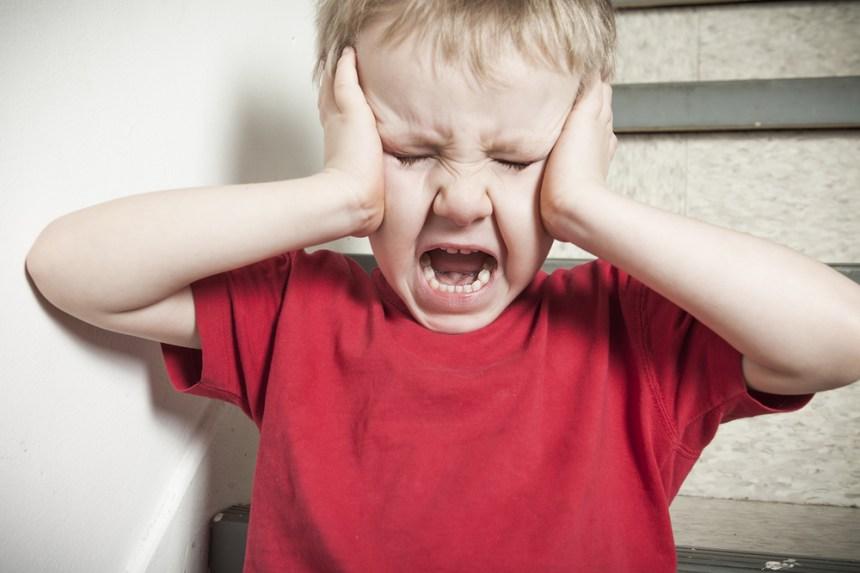 il ragazzo piange e si copre le orecchie