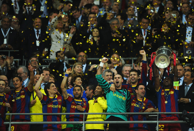 LONDON, ENGLAND - MAY 28:  Eric Abidal (R) of FC Barcelona lifts the trophy and celebrates with teammates after victory in the UEFA Champions League final between FC Barcelona and Manchester United FC at Wembley Stadium on May 28, 2011 in London, England.  (Photo by Laurence Griffiths/Getty Images)