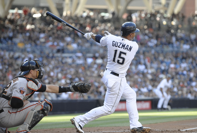 SAN DIEGO, CA - JULY 16:  Jesus Guzman #15 of the San Diego Padres hits a three-run homer during the first inning of a baseball game against the San Francisco Giants at Petco Park on July 16, 2011 in San Diego, California. (Photo by Denis Poroy/Getty Images)