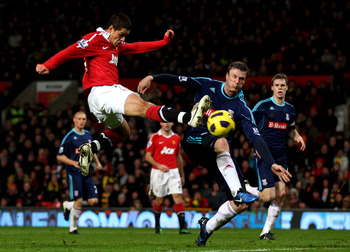 MANCHESTER, ENGLAND - JANUARY 04:  Javier Hernandez of Manchester United shoots at goal under pressure from Robert Huth of Stoke City during the Barclays Premier League match between Manchester United and Stoke City at Old Trafford on January 4, 2011 in M