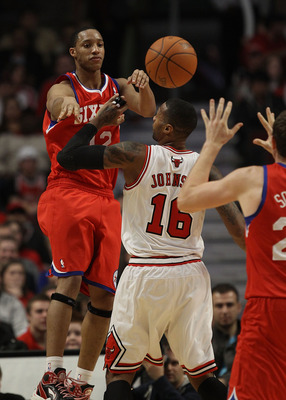 CHICAGO, IL - DECEMBER 21: Evan Turner #12 of the Philadelphia 76ers jumps to pass the ball over James Johnson #16 of the Chicago Bulls at the United Center on December 21, 2010 in Chicago, Illinois. The Bulls defeated the 76ers 121-76. NOTE TO USER: User