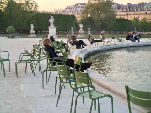 A woman sits at the edge of the Grand Bassin rond at the Jardins de Tuileries in Paris, France.