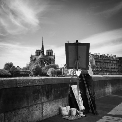 A painter sets up his easel along the banks of the Seine River near the Catherdral of Notre Dame in Paris, France.