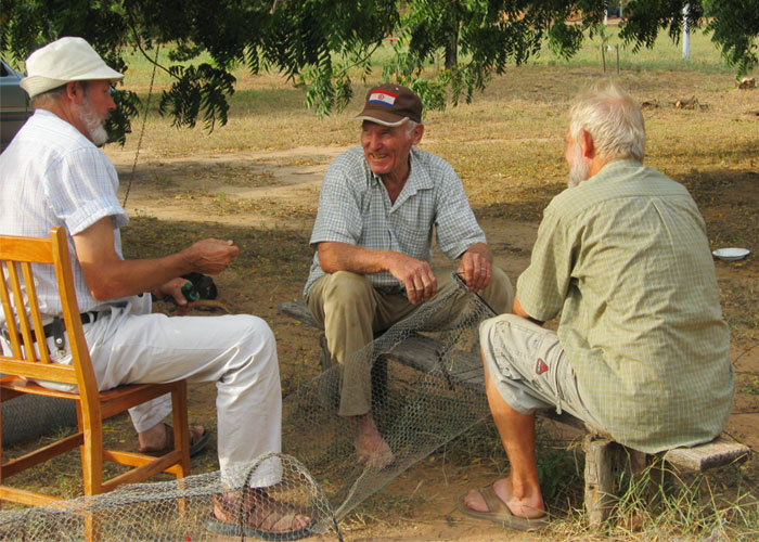 Three men sitting together and talking while repairing a net