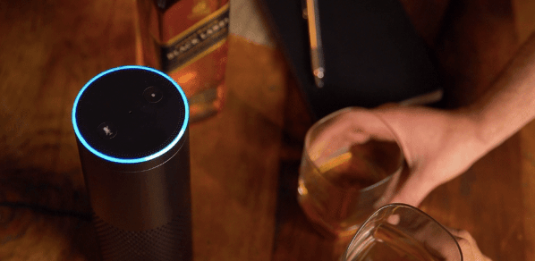 Johnnie Walker whiskey bottle, hand holding glass of whiskey and Amazon Alexa device