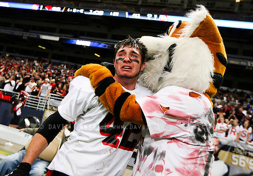 Jade Morgan (42) of the Lamar Tigers is hugged by the Lamar mascot while celebrating winning the 2012 MSHSAA football class 2 state championship game against the Blair Oaks Falcons at the Edward Jones Dome on November 24, 2012 in St. Louis, Missouri.
