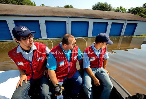 Lowe's employees survey flood damage while being boated in to help homeowners carry out possessions after a hurricane.
