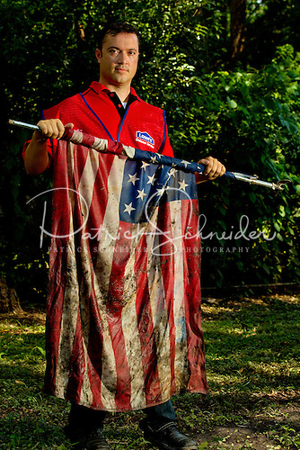 Photo of a Lowe's employee volunteer holding an American flag pulled from the mud during cleanup of Tropical Storm Debby in Live Oaks Florida.