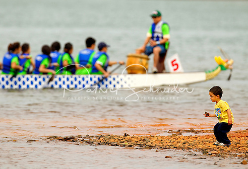 A young boy plays on the shoreline of Lake Norman during the 2012 Charlotte Dragon Boat Races.