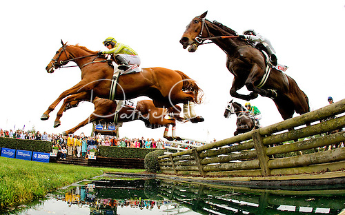 Photo of boys thoroughbred horses clearing a jump and water feature at the 2012 Charlotte Queen's Cup Steeplechase.