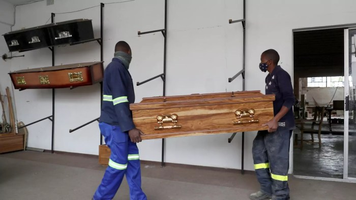 Workers carry a coffin to the display area at the Kingsize Coffins manufacturing plant, amid a nationwide coronavirus disease (COVID-19) lockdown, in Benoni, South Africa on January 25, 2021.