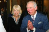 Britain's Prince Charles and Camilla entering a hall speaking to another person.