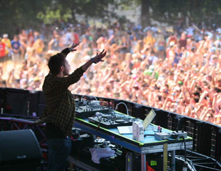 DJ on stage at Lollapalooza facing the crowd
