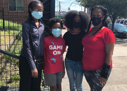 Jetia Byfield with three of her children Jahniya, Masai and Madeka stand outside the homeless shelter where they reside.