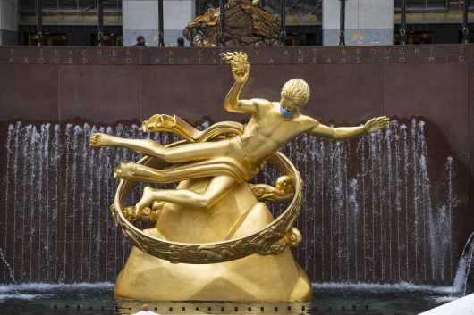 The Prometheus sculpture in Rockefeller Center features a PPE mask due to Covid-19 in Manhattan.