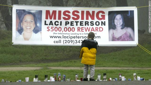 A young child stops to look at a memorial and a banner offering a half-million dollar reward for the safe return of Laci Peterson at the East La Loma Park  in Modesto, California, on January 4, 2003.