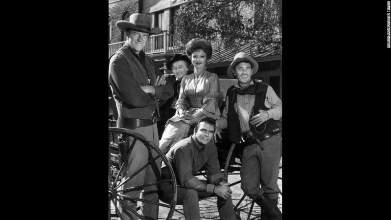 "The cast of the hit TV show ""Gunsmoke"" poses around a wagon in 1962. Behind Reynolds, from left, are James Arness, Milburn Stone, Amanda Blake and Ken Curtis."