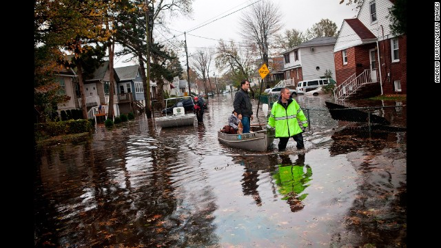 An emergency worker helps evacuate people stranded by flooding during Hurricane Sandy in 2012. A new report finds that the risk of financial loss for homeowners due to flooding is expected to grow as the climate changes