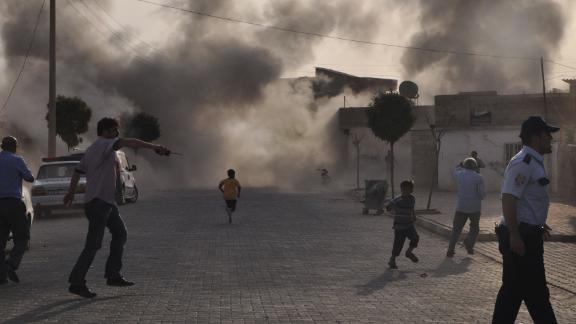 Smoke rises over the streets after a mortar bomb from Syria landed in the Turkish border village of Akcakale on October 3, 2012. Five people were killed. In response, Turkey fired on Syrian targets and its parliament authorized a resolution giving the government permission to deploy soldiers to foreign countries.
