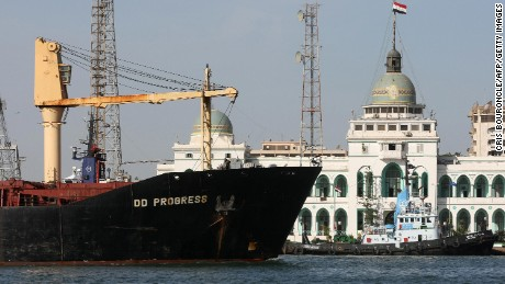 A cargo ship navigates in the Suez Canal, past the port authority building of Port Said, in 2008. The passageway hosts nearly 19,000 vessels each year.
