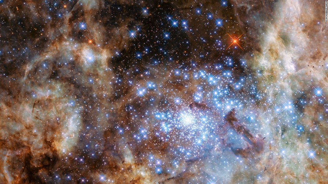 This image shows the central region of the Tarantula Nebula in the Large Magellanic Cloud. The young and dense star cluster R136, which contains hundreds of massive stars, is visible in the lower right of the image taken by the Hubble Space Telescope.