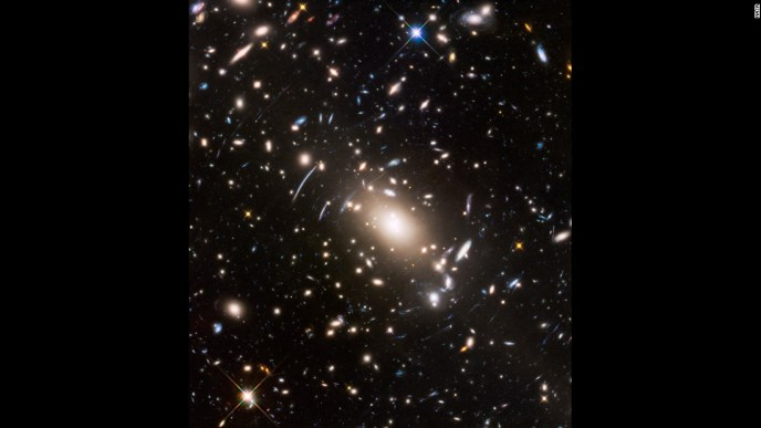 Gravitational lensing and space warping are visible in this image of near and distant galaxies captured by Hubble.