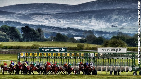 Runners break from the stalls in the back straight at Curragh racecourse.