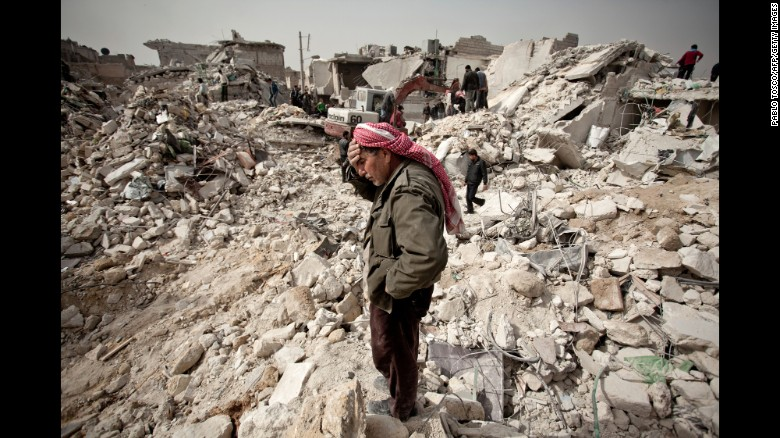 A Syrian man reacts while standing on the rubble of his house while others look for survivors and bodies in the Tariq al-Bab district of the northern city of Aleppo on February 23, 2013.