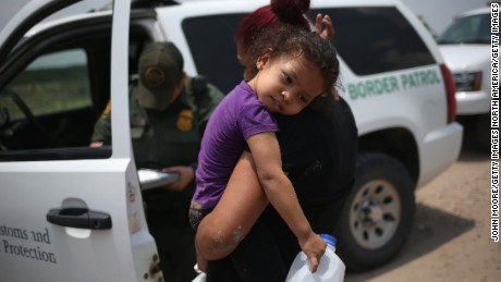 A mother and her 3-year-old child from El Salvador await transport to an immigrant processing center after they crossed the Rio Grande into the United States on July 24, 2014.