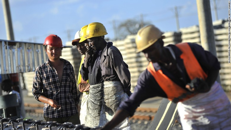 African, right, and Chinese workers, left, build railway track sections for the Mombasa-Nairobi Standard Gauge Railway (SGR) line in Tsavo, Kenya.