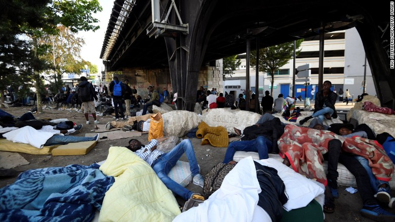 2 700 migrants relocated from  illegal  Paris camps   CNN Migrants and refugees rest by a railway bridge during the evacuation