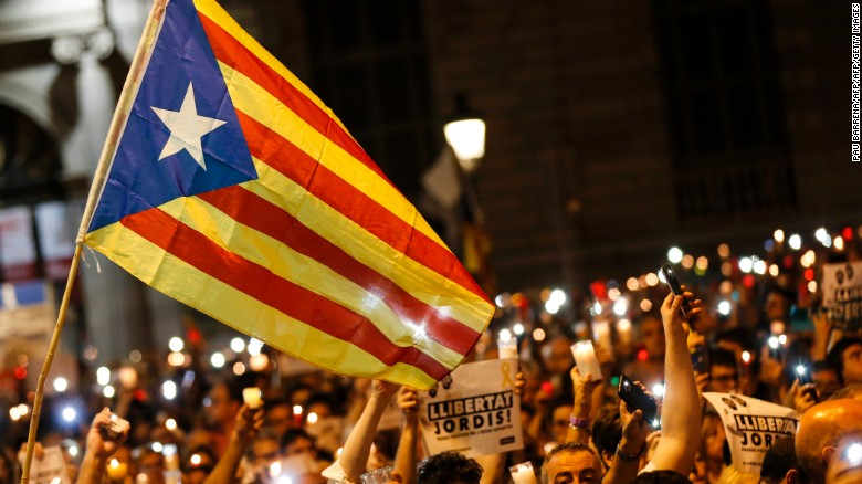 People hold candles and a Catalan flag during a demonstration in Barcelona against the arrest of two Catalan separatist leaders on October 17.