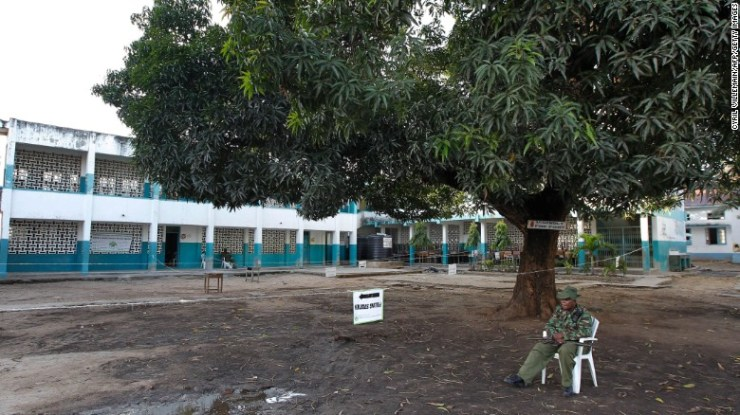 A Kenyan policeman sits outside an empty polling station in Mombasa on Thursday.