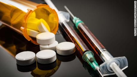 Opioid epidemic, drug abuse concept with closeup on two heroin syringes or other narcotics surrounded by scattered prescription opioids. Oxycodone is the generic name for a range of opioid painkillers; Shutterstock ID 706837198; Job: -