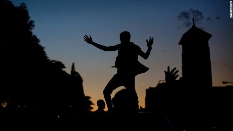 A Zimbabwean dances on the roof of a vehicle as the sun goes down in Harare on Tuesday.