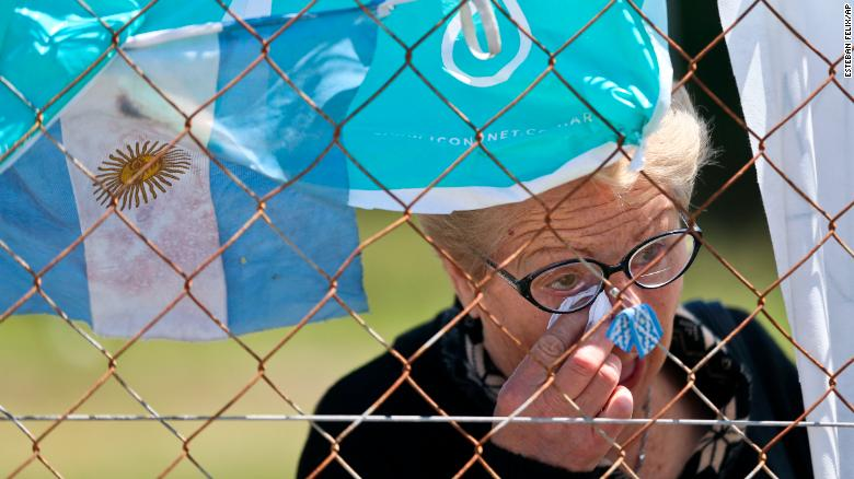 A woman cries Thursday in front of a fence enclosing the Mar del Plata naval base after learning that Argentina's navy announced that a sound detected during the search for the missing ARA San Juan submarine is consistent with that of an explosion.