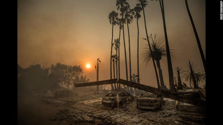 Smoke rises behind a leveled apartment complex as a wildfire burns in Ventura on Tuesday.