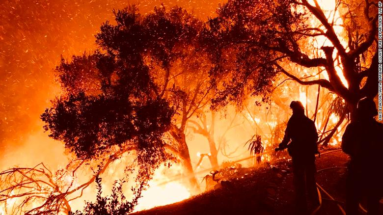 Firefighters battle a wildfire as it advances on homes in Carpinteria on December 10.