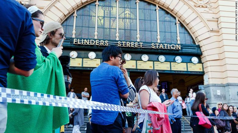 People gather at the scene of where the car ran over pedestrians on Flinders Street.
