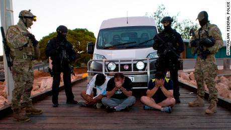 Three of the drug suspects, guarded by AFP officers, next to the van into which the drugs were loaded.