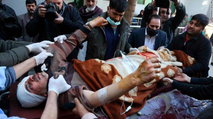 People carry an injured man to hospital after the suicide attack in Kabul on Thursday.
