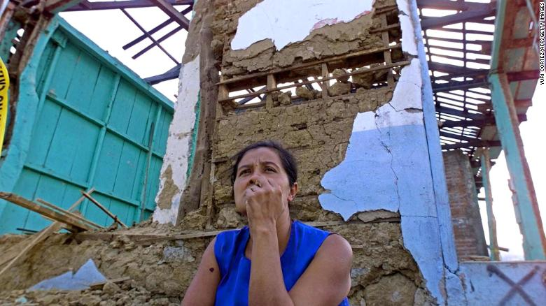A woman sits beside her earthquake-destroyed home in Armenia, El Salvador, on January 29, 2001.