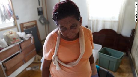 Carmen Rivera says she broke her arm sweeping water out of her living room.