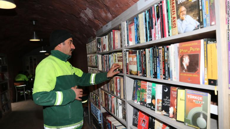 A garbage collector in Ankara browses for books at the library.